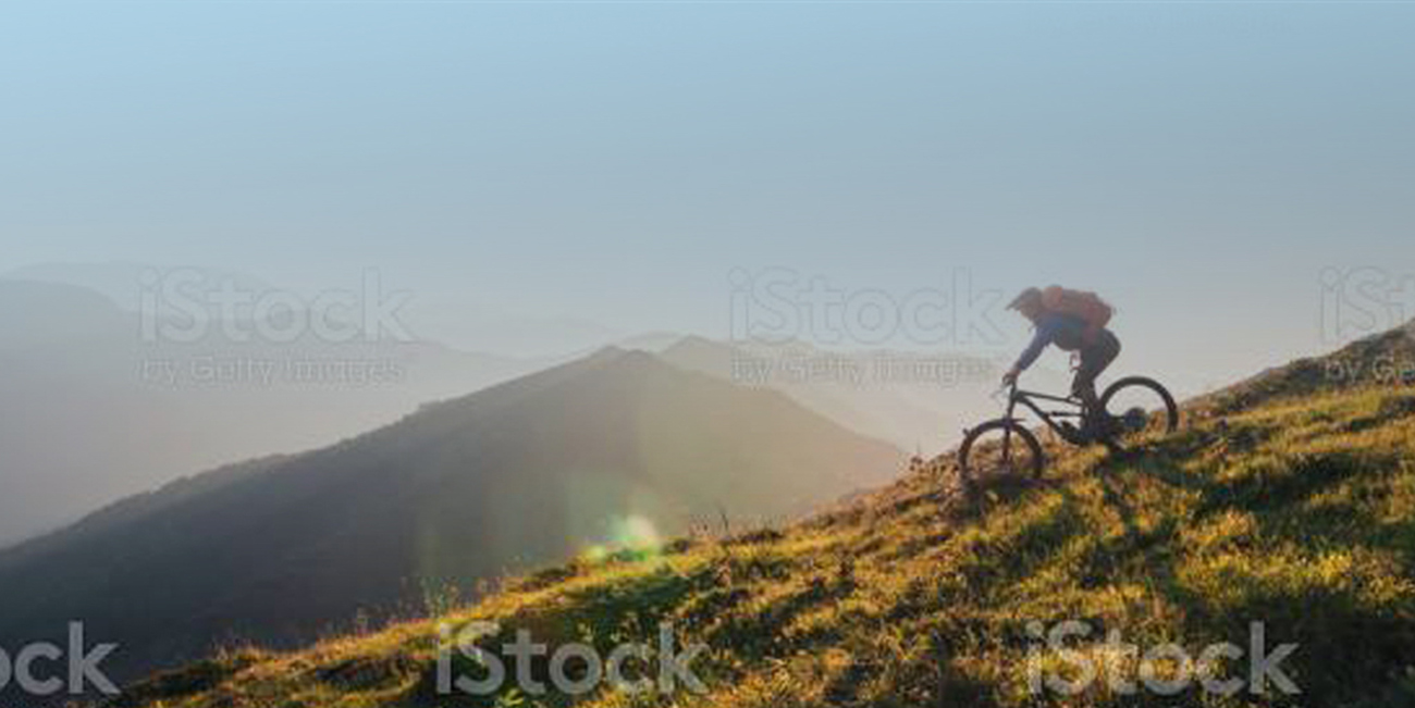 Mountain biker riding downhill in the mountains.